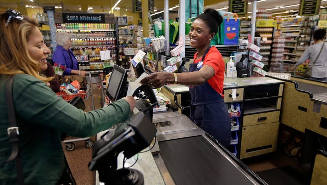 In this May 8, 2018, photo, Nadine Vixama, who emigrated from Haiti eight years ago, works as a cashier at a Whole Foods in Cambridge, Mass. Vixama has taken English classes and a program in store and customer service basics developed by the National Retail Federation trade group to gain work skills in retail. (AP Photo/Steven Senne)