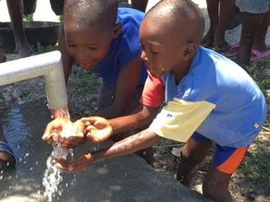 kids with hands in water well in haiti