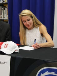 Rebecca Story signs her letter of intent to run at