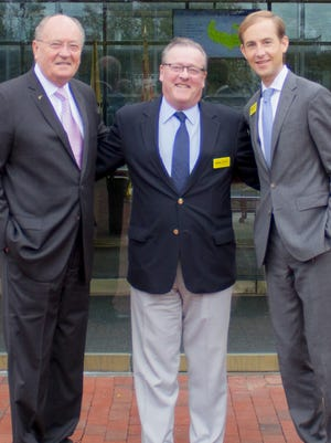 Dave Hardy, center, is congratulated by Jim Weichert, left, and James Weichert, right, at the opening of Weichert Property Management.