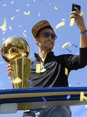 Warriors player Stephen Curry takes pictures during the team's NBA championship parade.