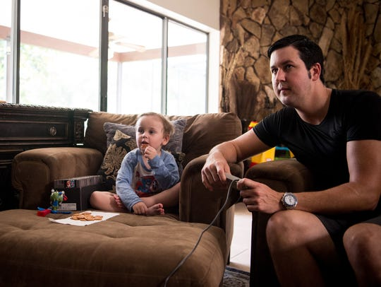 Steven Cook and his son, Ian Hannon-Cook, 3, play video
