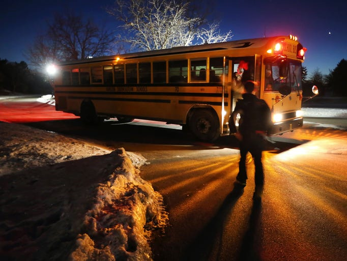 Kids make their way to the Hamilton Southeastern buses at 6:59 a.m. inside the Windermere subdivision at the Heritage Green stop as school has resumed on its normal schedule without a two-hour delay on Wednesday, January 29, 2014.