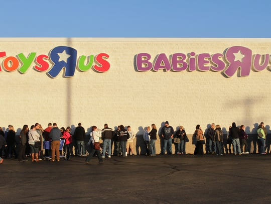 People stand in line waiting for Toys R Us to open