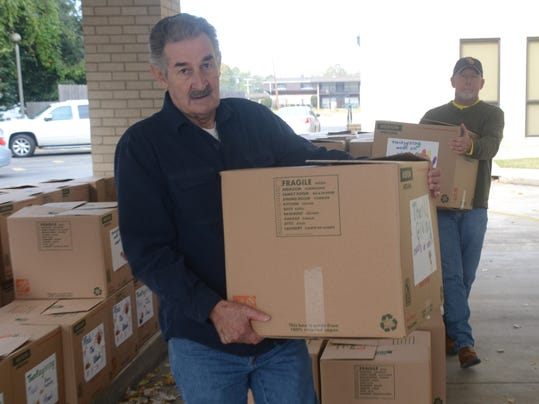 ANI Mission CenLa Ray Vercher (left) and Lane Howe, both Calvary Baptist Church members and volunteers with the church's Mission CenLa program, load Thanksgiving boxes into waiting cars Saturday, Nov. 23, 2014. One hundred boxes were delivered to needy f