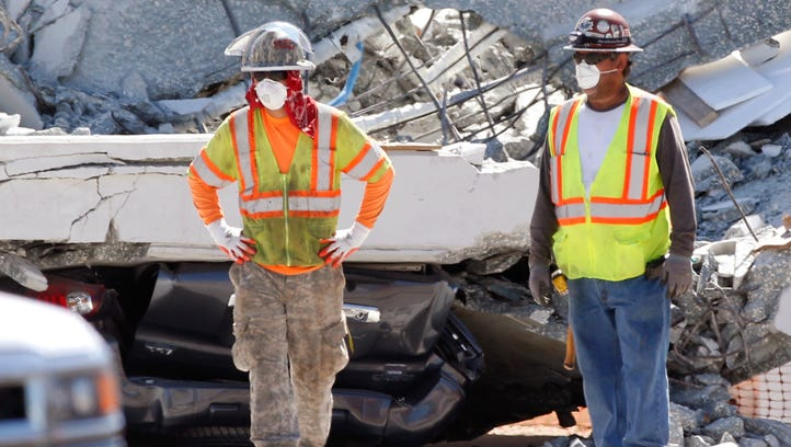 Workers stand in front of crushed cars under a section