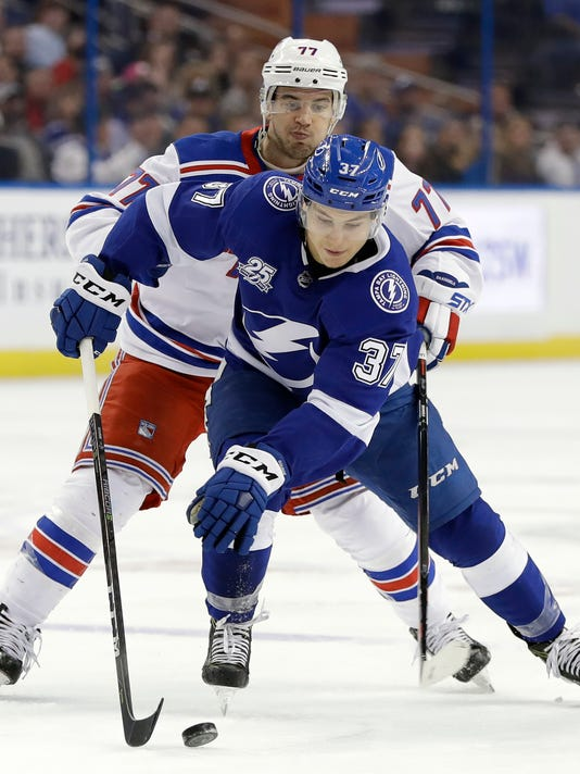 Tampa Bay Lightning center Yanni Gourde (37) beats New York Rangers defenseman Tony DeAngelo (77) to the puck during the second period of an NHL hockey game Thursday, March 8, 2018, in Tampa, Fla. (AP Photo/Chris O'Meara)
