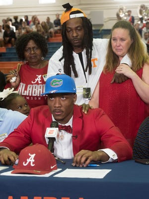 Escambia High Shcool standout, Jacob Copeland, center, announces his decision to attend the University of Florida on National Signing Day as his brother, Jesse Crosby, and his guardian Pamela Walker, right, react to the surprise announcement Wednesday, Feb. 7, 2018.