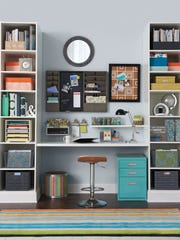 This image released by Home Goods shows a work space organized with baskets, and fabric and metal bins to keep a small study area organized. A teal blue file cabinet and striped rug add extra pops of color. (AP Photo/Homegoods.com)
