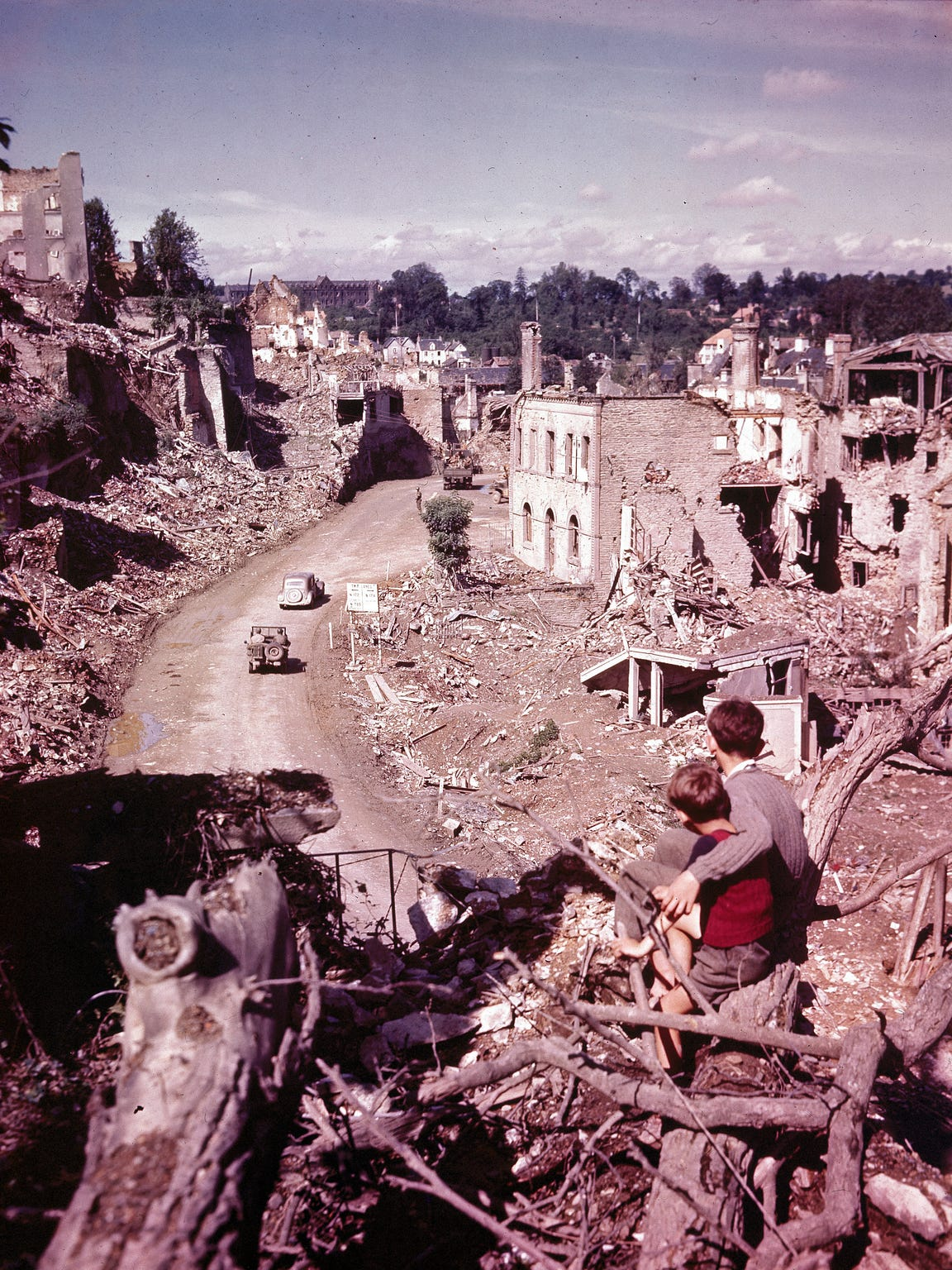 A view from the hilltop overlooking the road leading into St. Lo in July of 1944. during World War II.  Two French children in the foreground watch convoys and trucks of equipment go through their almost completely destroyed city en route to the front. (AP Photo)