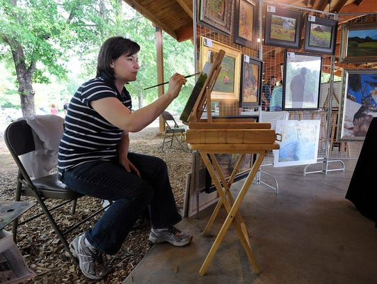 Jennifer Levins paints in her booth during the Flora