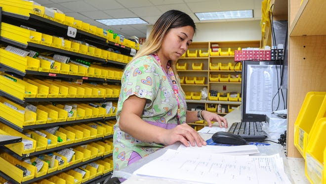 Hospital Pharmacy Technician Nikkie Aguilar enters patient medication information onto a terminal in the Guam Memorial Hospital pharmacy in Tamuning on July 26. The governor's office announced bonds have been sold to help the hospital pay its supply vendors this fiscal year and next year, or a total of $45 million.