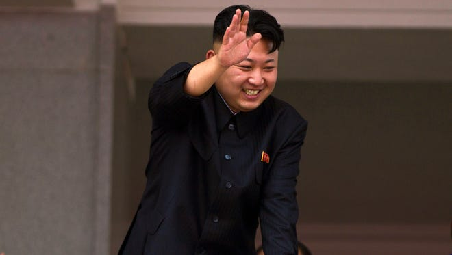 """North Korean leader Kim Jong Un leans over a balcony and waves to Korean War veterans cheering below at the end of a mass military parade on Kim Il Sung Square in Pyongyang to mark the 60th anniversary of the Korean War armistice on July 27, 2013. North Korea is warning that the release of a new American comedy about a plot to assassinate leader Kim Jong Un would be an """"act of war."""""""