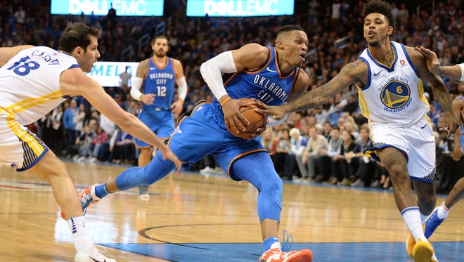 Oklahoma City Thunder guard Russell Westbrook (0) drives to the basket between Golden State Warriors forward Omri Casspi (18) and Golden State Warriors guard Nick Young (6) during the fourth quarter at Chesapeake Energy Arena.
