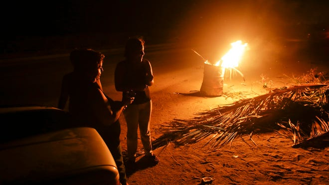 Residents gather by a bonfire set inside a steel drum as they stand outside guarding their homes as they face a fourth day without power and running water following the blow from Hurricane Odile in Los Cabos, Mexico, on Sept. 17, 2014.
