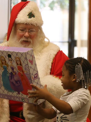Taliya Fowler, 3, shows her new toy to Santa during the Rizpah Network's third annual 3N1 Prayer Breakfast, Summit & Imagine Holiday Celebration at the DoubleTree Hotel on Saturday, Dec. 12, 2015. The gifts were made possible by the Jackson Police Department, SoulQuest Church, individual donations and the Rizpah Network.