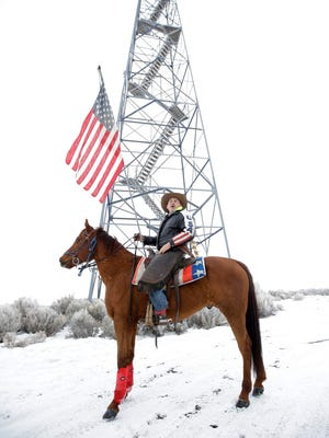 In this Jan. 7, 2016, file photo, Dwane Ehmer, a supporter of the group occupying the Malheur National Wildlife Refuge, holds a U.S. flag as he rides his horse next to a manned watch tower near Burns.