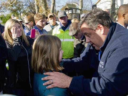FILE - In this Nov. 5, 2012, file photo, New Jersey Gov. Chris Christie gives 9-year-old Ginjer Doherty a pep talk while visiting residents and first responders a week after Superstorm Sandy.