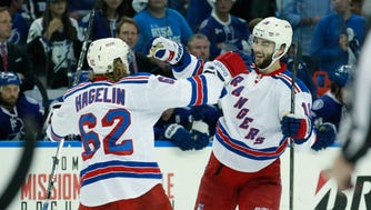 New York Rangers center Derick Brassard (16) celebrates his empty net goal with New York Rangers left wing Carl Hagelin (62) during the third period of game six of the Eastern Conference Final of the 2015 Stanley Cup Playoffs at Amalie Arena.