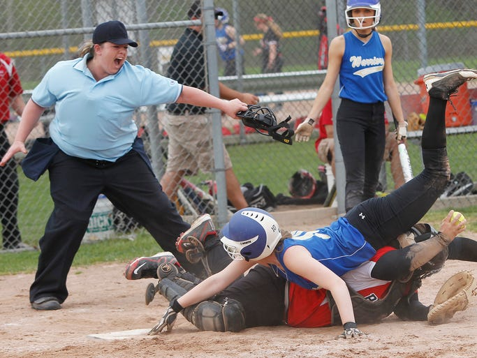 Schroeder's Abby Broomfield, top, is called out at home as Penfield's Nicole Sheffer shows the umpire the ball from the bottom of a pile at home plate during softball action between the Penfield Patriots and Webster Schroeder Warriors in Webster Friday evening, May 9, 2014.