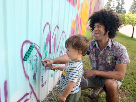 Cory Bennett, right, helps Olsen Fisher, 3, paint part of a heart at the Poulsbo Community Mural on Thursday. The site is proposed for the future Poulsbo Skate Park. The community is invited on Saturday to help paint the mural.