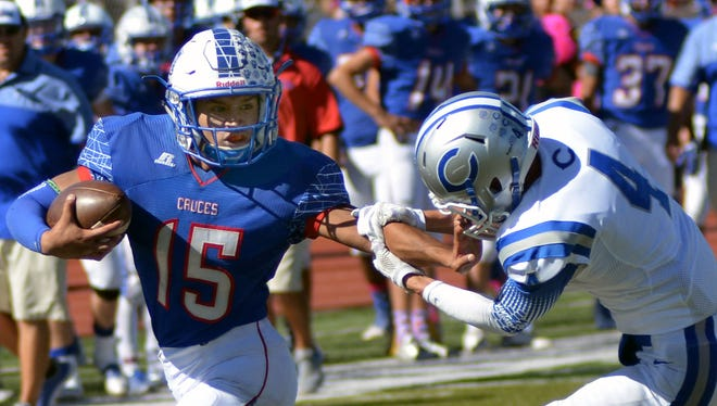 Las Cruces High's Brandon Baeza uses a stiff arm to avoid  Carlsbad's Jordin Molina during Saturday's game at Field of Dreams.
