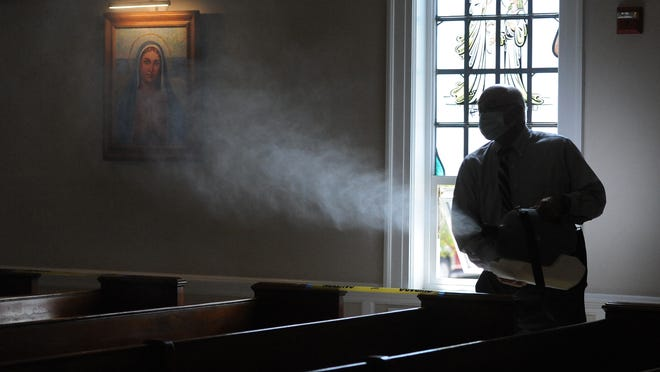 Deacon Steven Minninger sprays a disinfectant among the pews after the 9 a.m. Mass at St. Francis Xavier Parish on Sunday. The spraying was to be conducted between each weekend Mass and was one of several precautions in place as the Hyannis church reopened to worshippers after a two-month closure during the coronavirus pandemic.