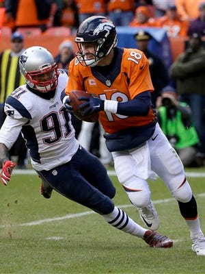 Denver Broncos quarterback Peyton Manning evades a tackle by New England Patriots outside linebacker Jamie Collins (91) during the first half of the NFL football AFC Championship game between the Denver Broncos and the New England Patriots, Sunday.