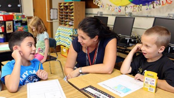 Second-grade teacher Julie Shook works with Anthony
