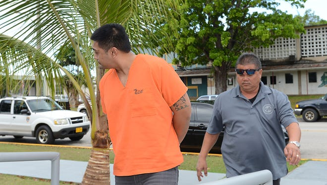 David Villena Quitugua turns his head as he is escorted to the Guam Police Department Hagåtña precinct in May 2013.