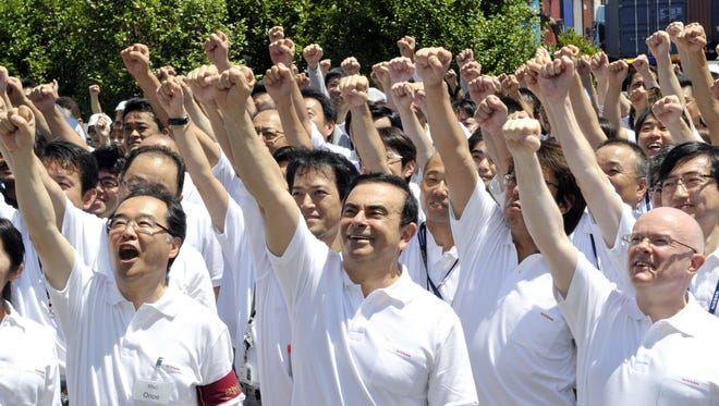 Japan's auto giant Nissan Motor president Carlos Ghosn (C) and workers of Honmoku wharf facility raise their fists in the air and yell slogans after Ghosn inspected the facility, which has recovered from March 11, 2011, earthquake in Yokohama, suburban Tokyo on July 16, 2011.