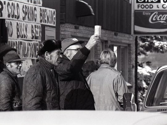"""""""Billy"""" in hand, a patron of the Side Bar in Cold Spring salutes passing trucks at the beer's release event in 1977."""