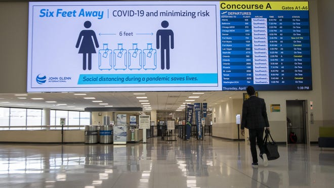 A video board warns travelers to maintain a six-foot distance inside John Glenn International Airport in Columbus on Thursday, April 2, 2020. The airport has seen a significant drop-off in traffic due to travel restrictions for the COVID-19 coronavirus pandemic.