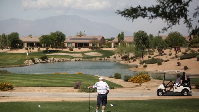 A golfer waits at the tee box for putters to wrap up their game at Sun City Shadow Hills on Tuesday in Indio. The homeowners association of Sun City Shadow Hills has incorporated desert landscaping into their golf course, as can be seen on the right side of the photo.