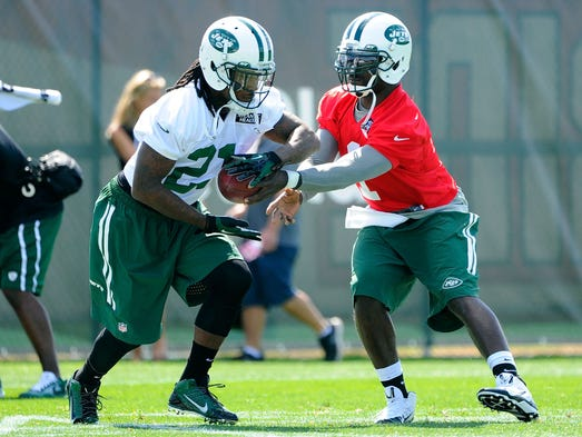 New York Jets quarterback Michael Vick hands off to running back Chris Johnson during drills at training camp at SUNY Cortland.