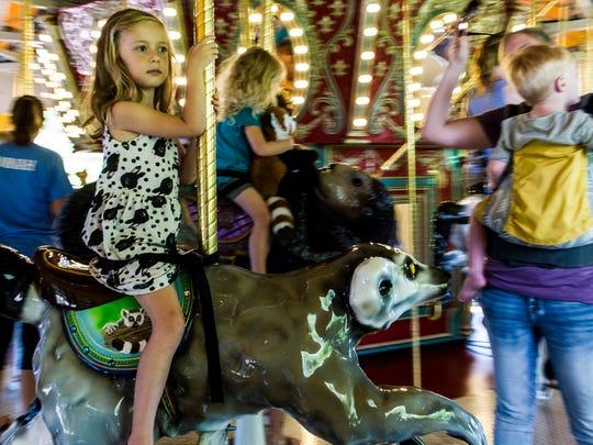 Neila McCauley, 4, rides a lemur on the new Engelbrecht Carousel at the Mesker Park Zoo & Botanical Garden in Evansville, Ind., on Wednesday, June 28, 2017. McCauley rode alongside her sister, Larkin McCauley, her mother, Jessa McCauley and her brother, Truitt McCauley.