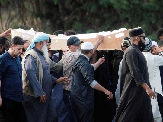 Mourners proceed with the coffin of a shooting victim, slain by an Australian white supremacist gunman who went on a killing spree at two mosques, at the Memorial Park cemetery in Christchurch on March 20, 2019.  A Syrian refugee and his son were buried in New Zealand on March 20 in the first funerals for those killed in the twin mosque massacre as Kiwis braced for days of emotional farewells following the mass slayings.