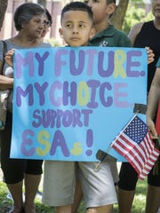 Eduardo Elias, 10, holds up a sign in support of the