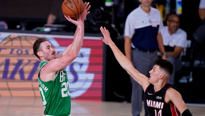 Boston Celtics' Gordon Hayward (20) attempts a shot as Miami Heat's Tyler Herro (14) defends during the second half of an NBA conference final playoff basketball game, Saturday, Sept. 19, 2020, in Lake Buena Vista, Fla.
