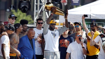 epa05385116 Former Cleveland Browns NFL player Jim Brown (3-L) looks on as Cleveland Cavaliers forward LeBron James (C) raises the NBA championship trophy during the Cleveland Cavaliers NBA Championship Parade and Rally in downtown Cleveland, Ohio, USA, 22 June 2016. The Cleveland Cavaliers defeated the Golden State Warriors in game 7 of the NBA Finals to be crowned the 2016 NBA champions.  EPA/DAVID MAXWELL ORG XMIT: DMX41