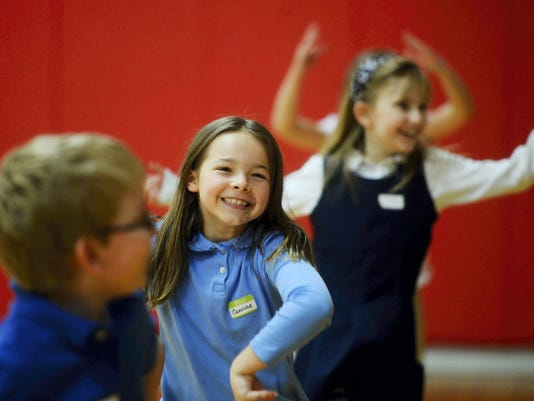 Third graders, from left Cameron Croom, Caroline Kearns, and Grace Stover, grin as the dance speeds up during a dance session at York Country Day School Wednesday.