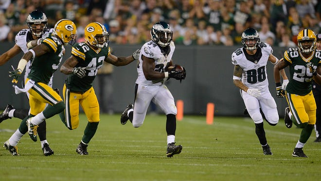Philadelphia Eagles running back Kenjon Barner (34) breaks away for a run against the Green Bay Packers in the second quarter during Saturday night's preseason game at Lambeau Field.