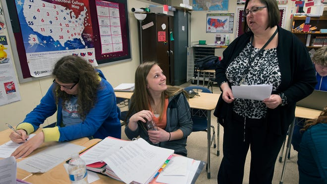 From the left, George Tatlas, a senior, and Erica Shearer, a junior listen to Sue Witmer during an AP US government class at Northeastern High School. Witmer said she stresses civility as students discuss presidential politics.