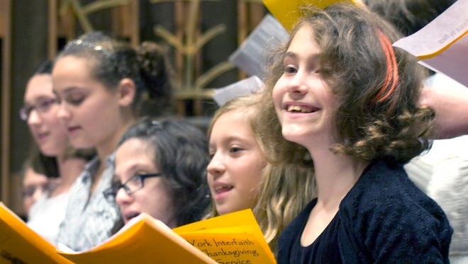 """In this 2010 file photo, Estelle Chock, 9, smiles at the audience during the Temple Beth Israel Adult and Youth Choir's singing of """"Peace by Piece"""" during the Interfaith Thanksgiving Service."""