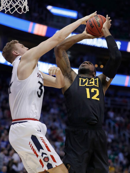 Saint Mary's center Jock Landale (34) blocks the shot of Virginia Commonwealth forward Mo Alie-Cox (12) during the first half of a first-round game in the NCAA men's college basketball tournament Thursday, March 16, 2017, in Salt Lake City. (AP Photo/George Frey)