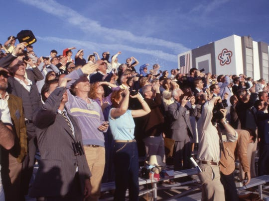 Spectators watching space shuttle Columbia launch on April 12, 1981, from a launch viewing area at Kennedy Space Center. It was the first shuttle launch. The Vehicle Assembly Building is in the background.