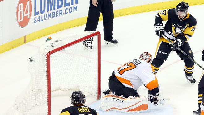Nov 27, 2017; Pittsburgh, PA, USA;  Pittsburgh Penguins center Sidney Crosby (87) scores the game winning goal in overtime past Philadelphia Flyers goalie Brian Elliott (37) at PPG PAINTS Arena. The Penguins won 5-4 in overtime. Mandatory Credit: Charles LeClaire-USA TODAY Sports