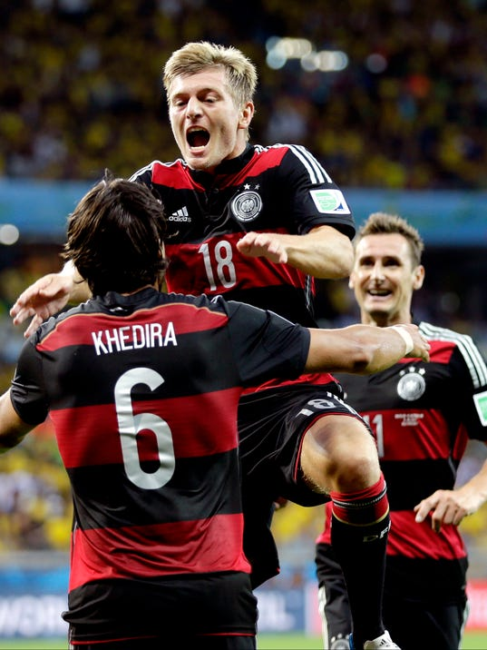 Germany's Toni Kroos (18) celebrates with Sami Khedira (6) and Miroslav Klose, right, after scoring his side's fourth goal during the World Cup semifinal soccer match between Brazil and Germany at the Mineirao Stadium in Belo Horizonte, Brazil, Tuesday, July 8, 2014. (AP Photo/Natacha Pisarenko)