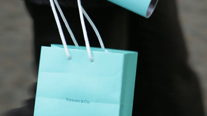 A shopper carries a purchase from Tiffany and Co.