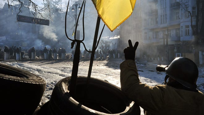 An anti-government protester uses binoculars to look at police troops at a barricade on Grushevsky street in Kiev, on Feb. 4, 2014. The crisis has sparked tensions between the West, which is considering sanctions against Ukrainian officials, and Russia, which has accused the EU and US of interference in Ukraine.
